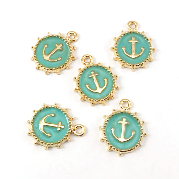green and gold jewelry charms that look like anchors