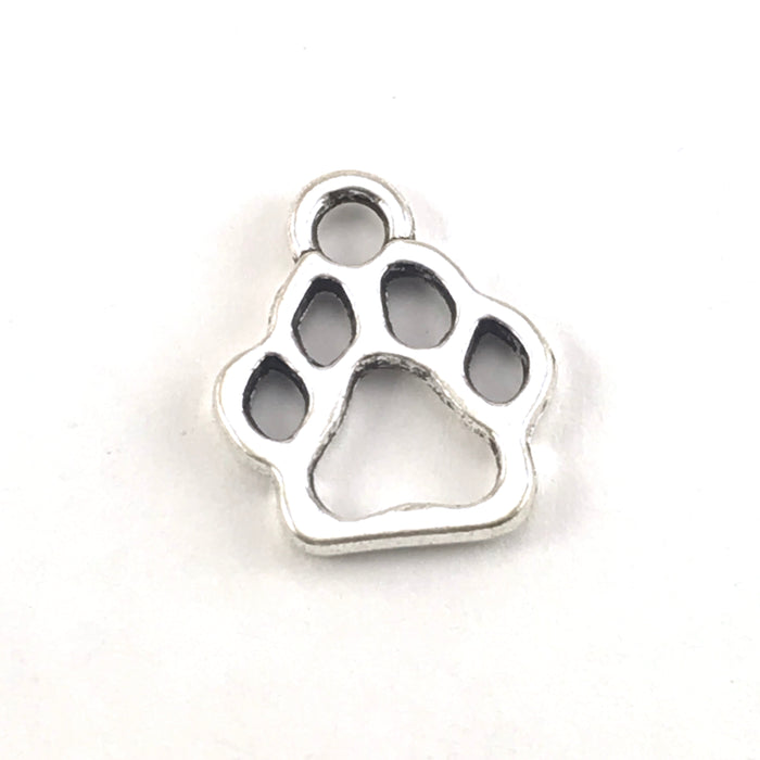 close up of silver colour jewelry charms shaped like paw prints