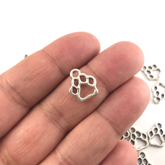silver colour jewelry charm shaped like a paw print, sitting on a hand to show scale