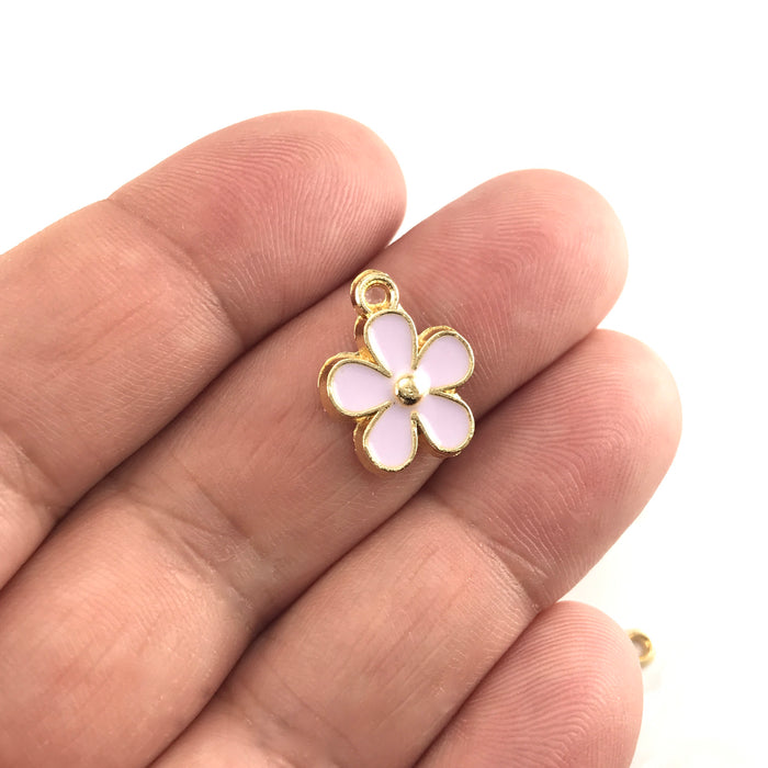 purple and gold colour jewerly charms that look like flowers, sitting on a hand to show scale