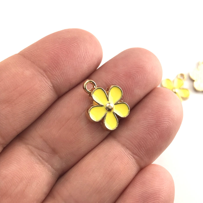 yellow and gold colour jewerly charms that look like flowers, sitting on a hand to show scale