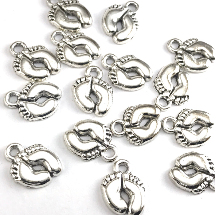 silver colour jewerly charms shaped like feet