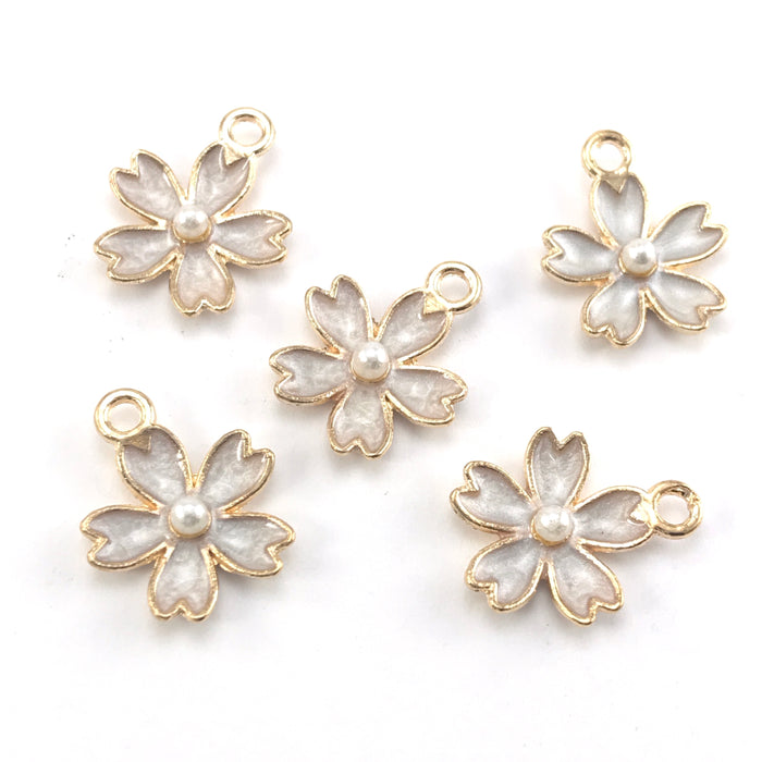 white and gold jewerly charms shaped like flowers