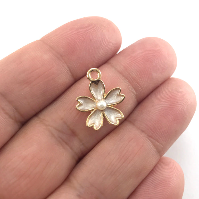 white and gold jewerly charms shaped like flowers, sitting on a hand to show scale