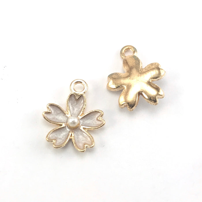 front and back of white and gold jewerly charms shaped like flowers