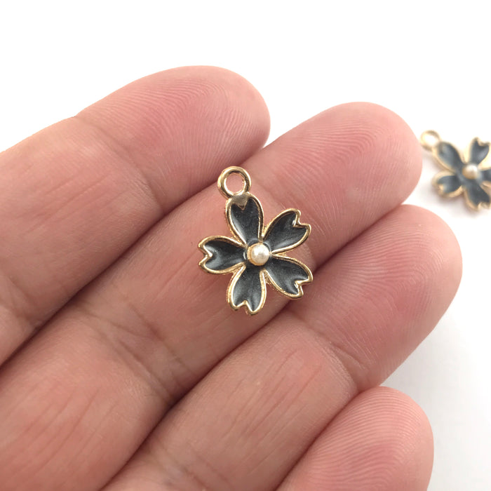 black and gold colour jewerly charms in the shape of flowers, sitting on a hand to show scale