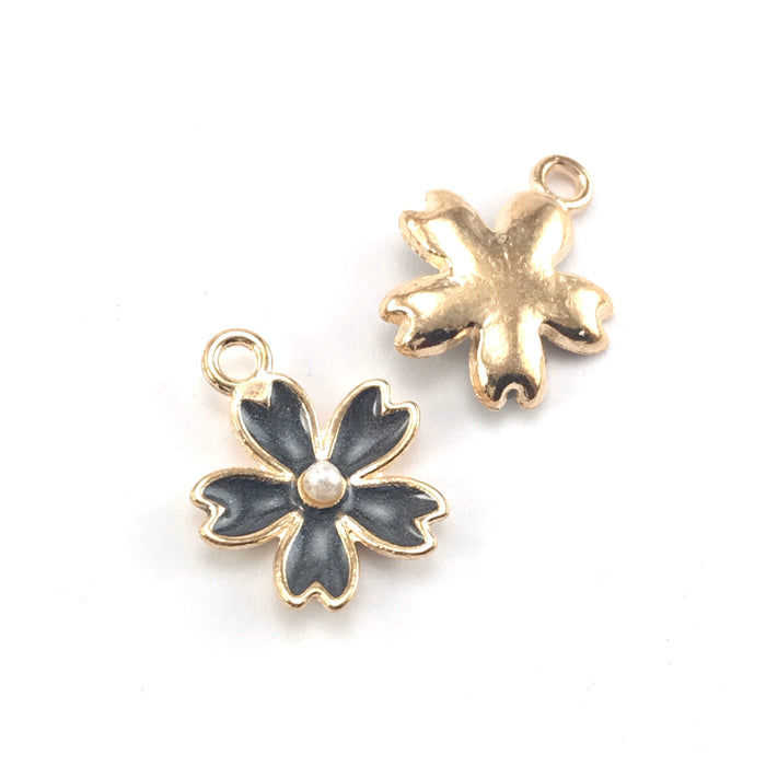 front and back of black and gold colour jewerly charms in the shape of flowers
