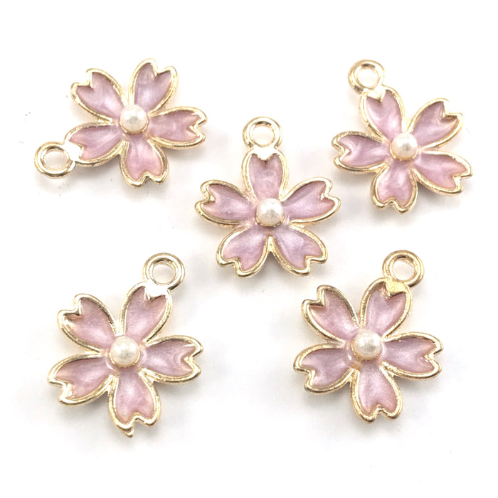 purple and gold jewerly charms in the shape of flowers