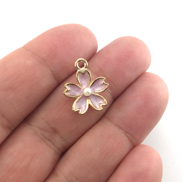 purple and gold jewerly charms in the shape of flowers, sitting on a hand to show scale