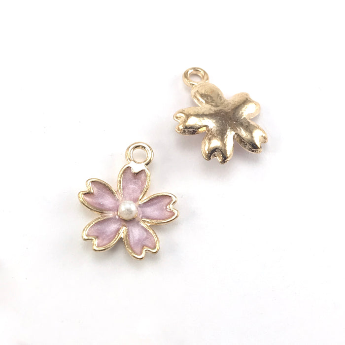 front and back of purple and gold jewerly charms in the shape of flowers