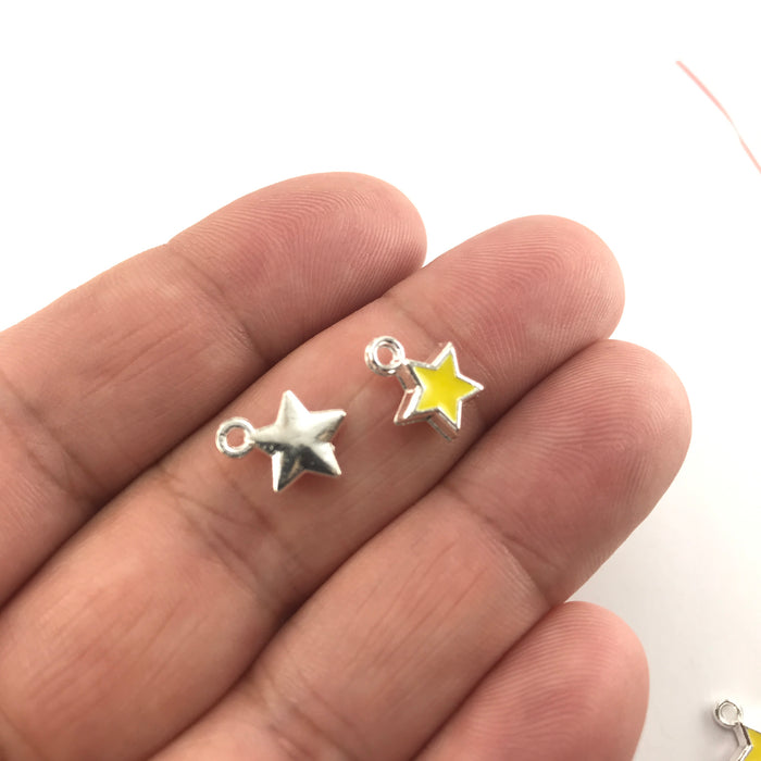 yelllow and silver star shaped jewerly charms, sitting on a hand to show scale