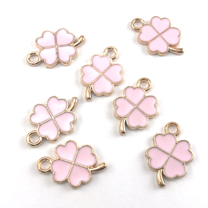 pink and gold colour jewelry charms that look like founr leaf clovers