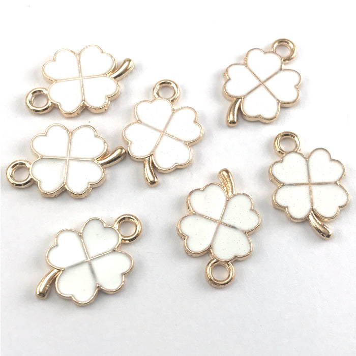 four leaf clover shaped jewerly charms that are white and gold