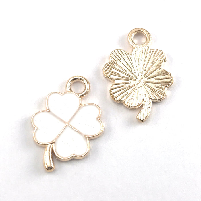 front and back of four leaf clover shaped jewerly charms that are white and gold