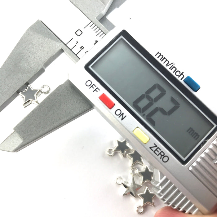 grey and silver colour star shaped jewelry charms on a digital ruler showing 8.2mm