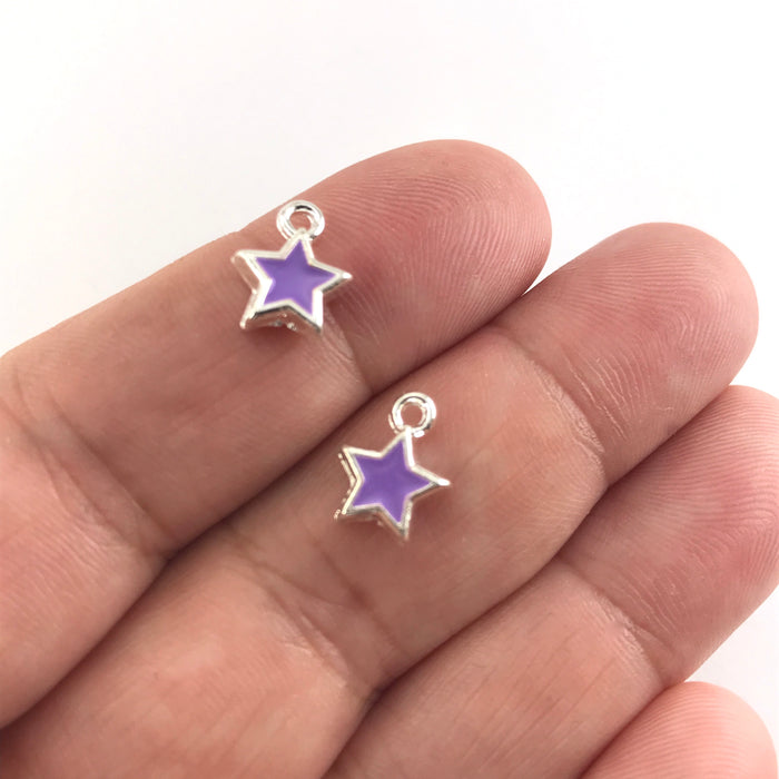 purple and silver star shaped jewerly charms, sitting on a hand to show scale