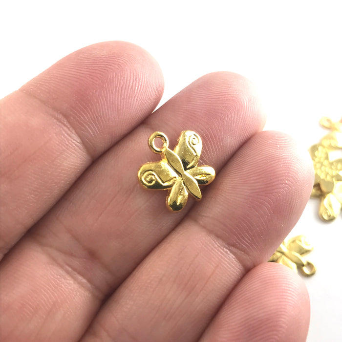 gold colour butterfly shaped jewerly charms, sitting on a hand to show scale