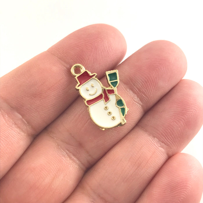 white red and green jewerly charms that look like snowmen, sitting on a hand to show scale