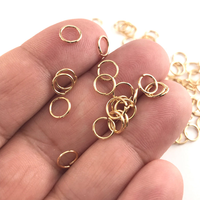 gold colour open metal jump rings, sitting on a hand to show scale