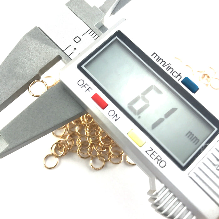 gold colour open metal jump rings on an electronic ruler showing 6.1mm