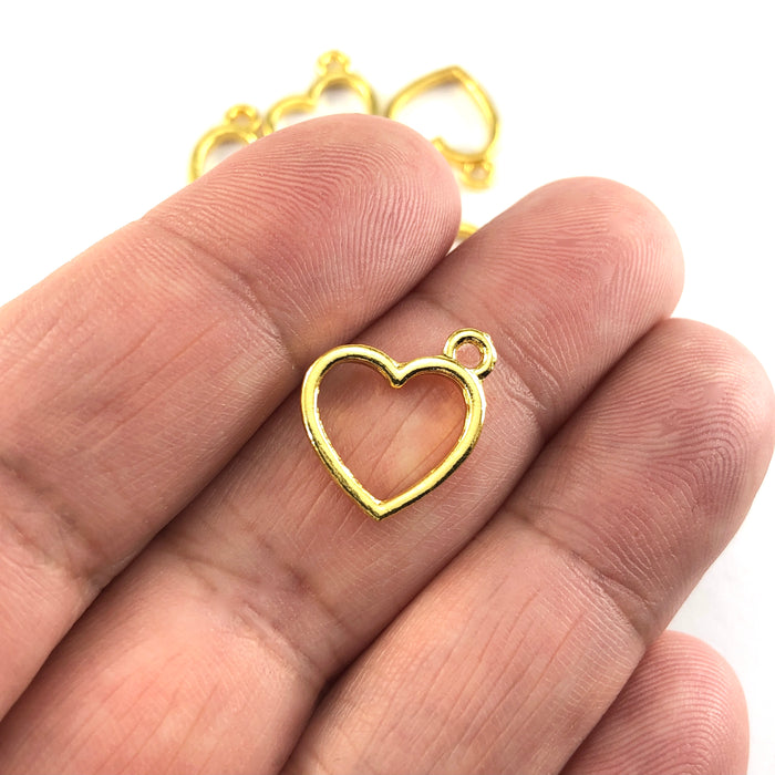 gold colour heart shaped jewerly charms, sitting on a hand to show scale