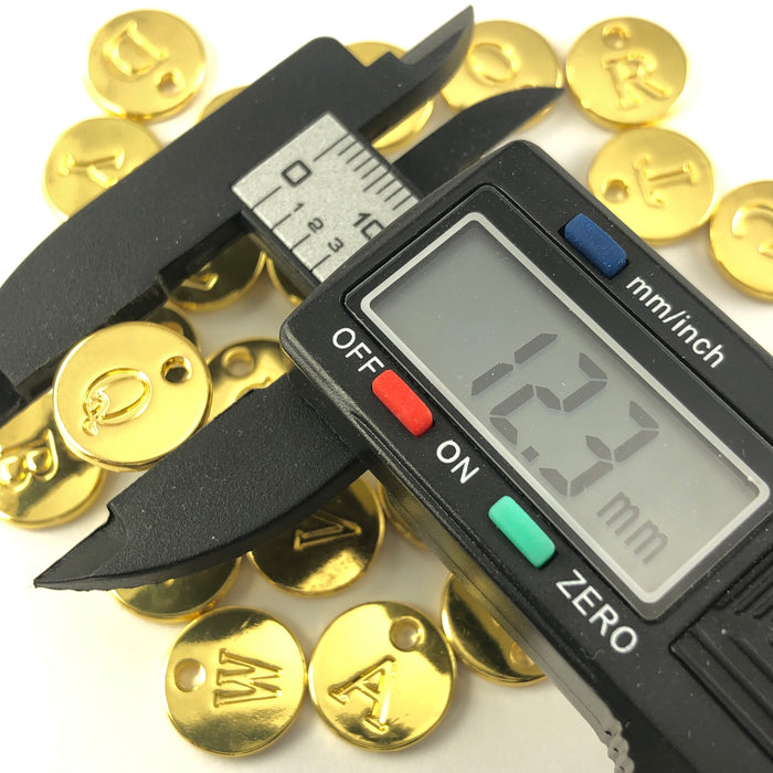 gold colour round charms with letters stamped on them, on a digital ruler that reads 12.3mm