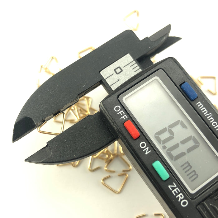 gold colour triangle shaped jump rings, on a digital ruler that reads 6mm