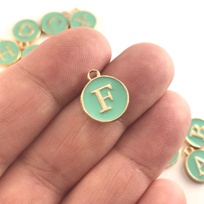 Green and gold round letter charms, sitting on a hand to show scale