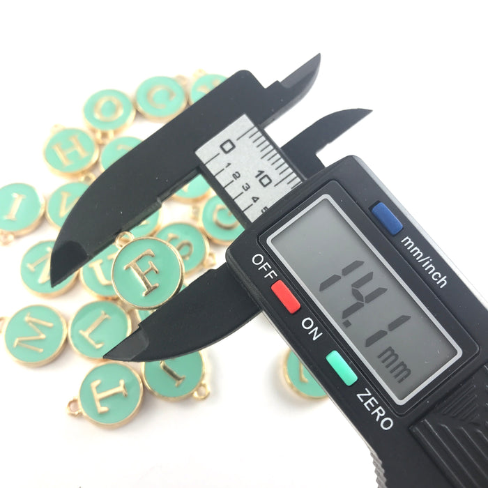 Green and gold round letter charms, on an electronic ruler that reads 14.1mm