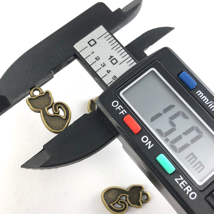 cat shaped bronze colour jewerely charms, on a digital ruler that reads 15mm