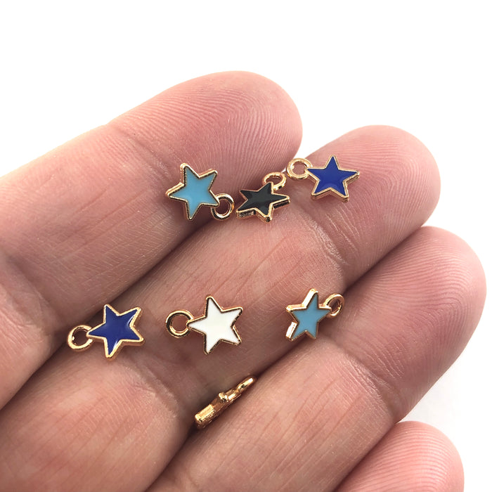 Star shaped jewelry charms in mixed colours, sitting on a hand to show scale