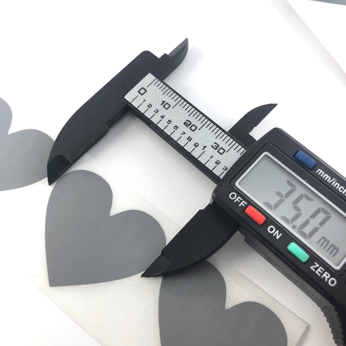 gray heart shaped stickers, on a digital ruler that reads 35mm