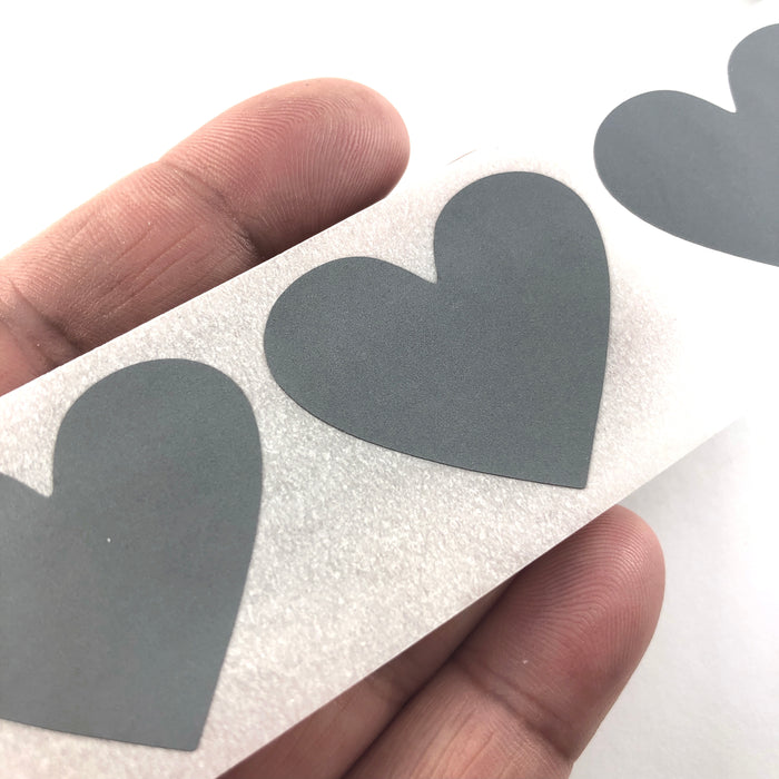 gray heart shaped stickers, sitting on a hand to show scale