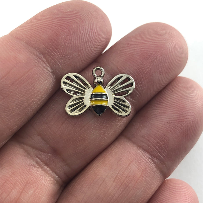 bee shaped charms that are silver, black and yellow, sitting on a hand to show scale