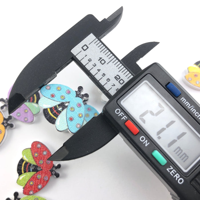 multi coloured buttons that look like bees, on a digital ruler that reads 21.1mm