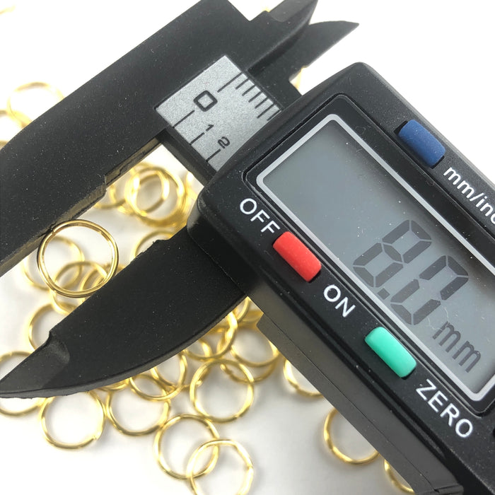 gold colour open jump rings, on a digital ruler that reads 8mm