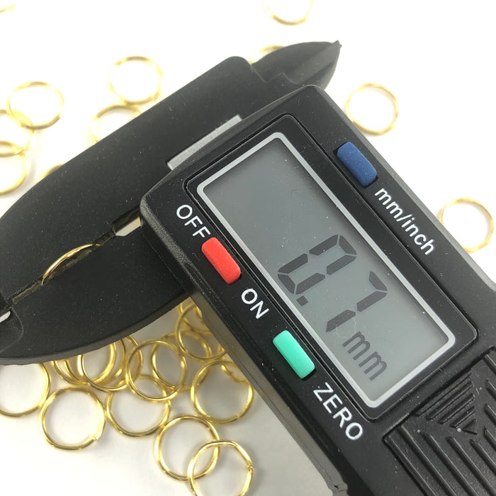 gold colour open jump rings, on a digital ruler that reads .7mm