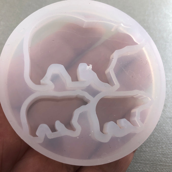 round silicone mold with bear shapes, on a hand to show scale