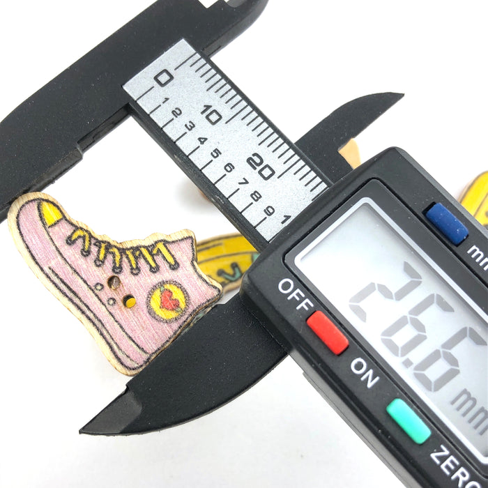 multi coloured buttons that are shaped like shoes, on a digital ruler that reads 26.6mm