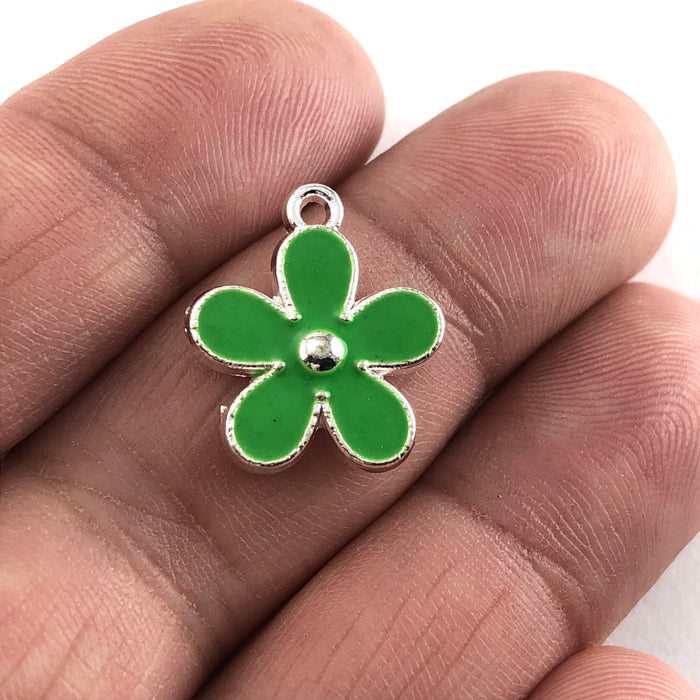green and silver flower shaped jewerly charm, on a hand to show scale