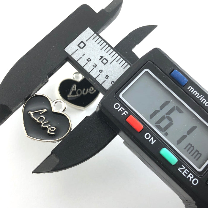 heart shaped black and silver charms with the word love on them, on  a digital ruler that reads 16.1mm