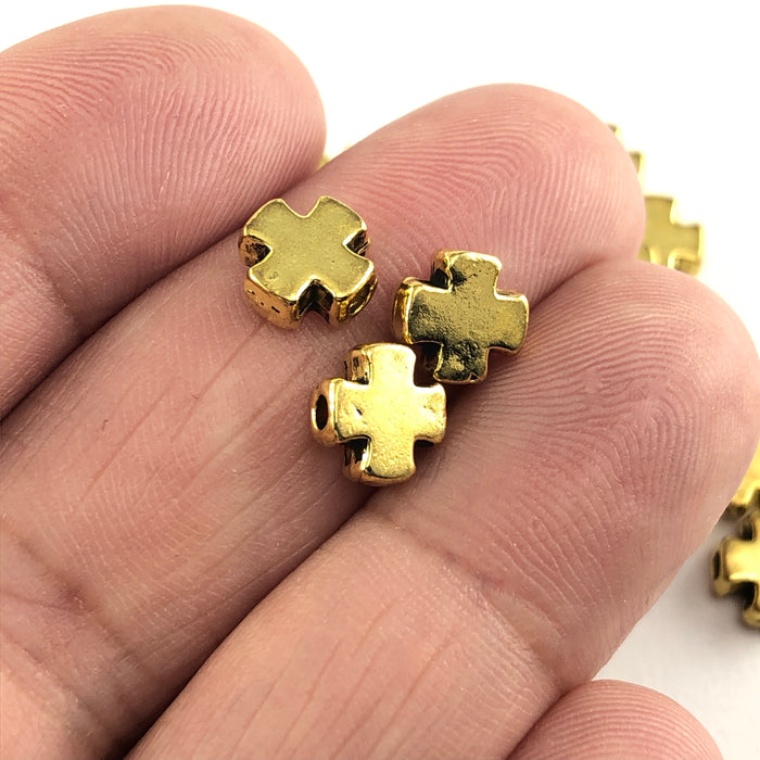 cross shaped gold jewerly beads, on a hand to show scale