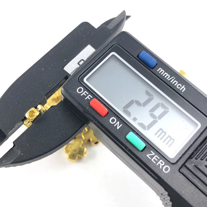 cross shaped gold jewerly beads, on a digital ruler that reads 2.9mm
