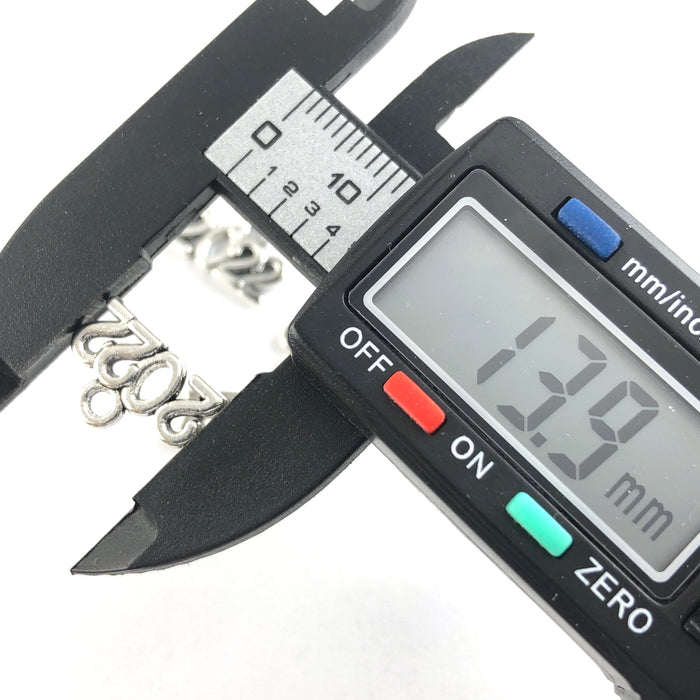silver jewerly charms in the shape of 2022, on a digital ruler that reads 13.9mm