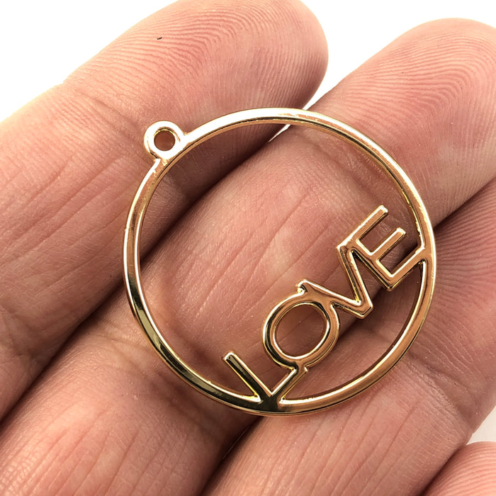 round open back bezels that have the word love in them, witting on a hand to show scale
