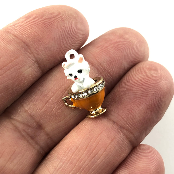 Jewelry charms that look like a white dog in an orange teacup with rhinestones around the rim of the cup, sitting on a hand to show scale
