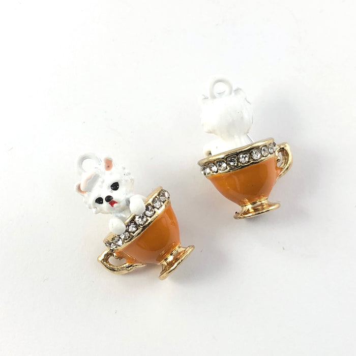 front and back of Jewelry charms that look like a white dog in an orange teacup with rhinestones around the rim of the cup