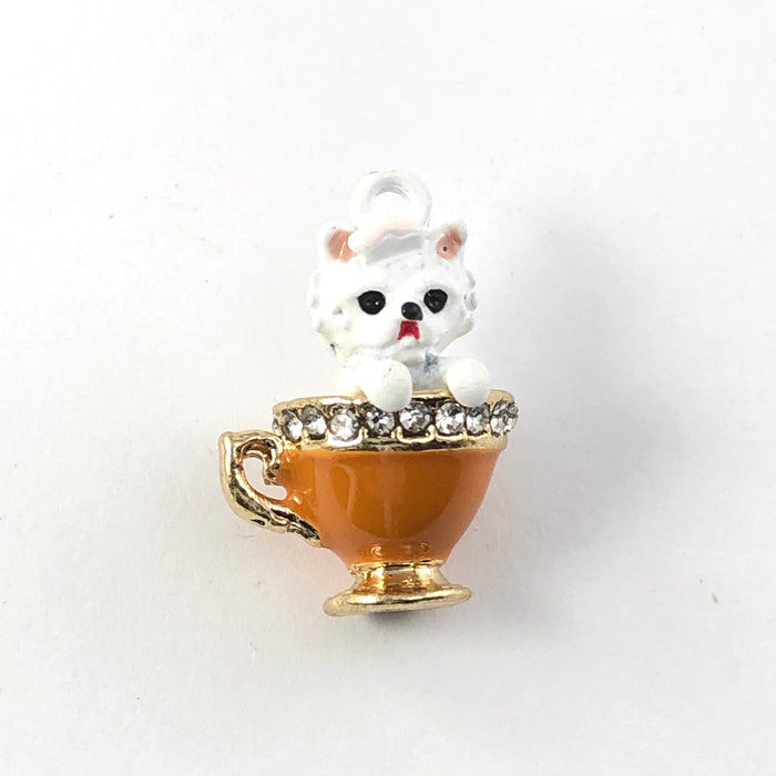 Jewelry charms that look like a white dog in an orange teacup with rhinestones around the rim of the cup