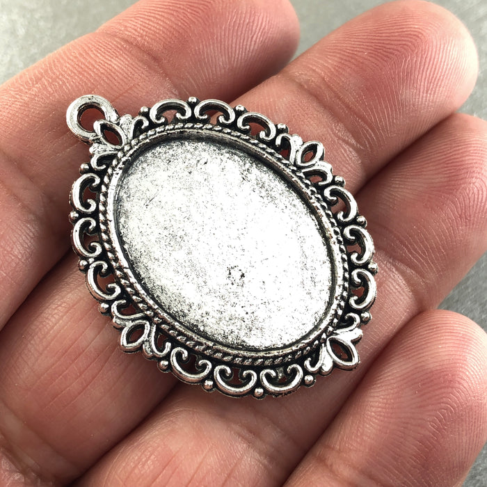 oval silver colour cabochon trays, sitting on a hand to show scale