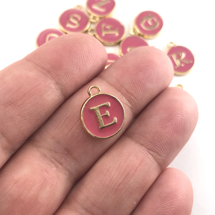 Pink and gold round letter charms, sitting on a hand to show scale
